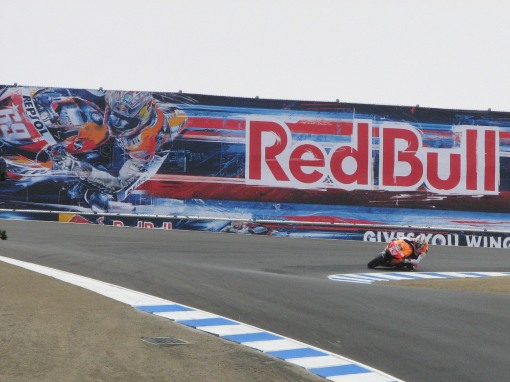 Nicky Hayden enters the infamous Corkscrew turn at Laguna Seca, in front of a Red Bull ad in the background featuring his likeness.