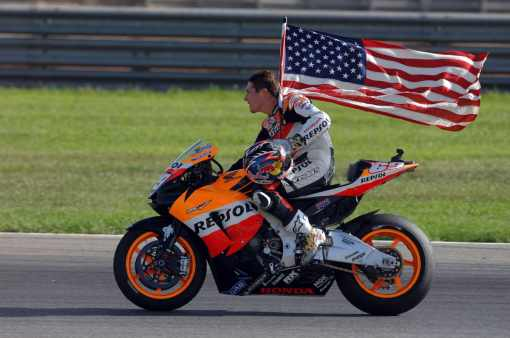 Nicky Hayden with American flag riding helmetless, after clinching the 2008 MotoGP World Championship aboard his Repsol Honda grand prix motorcycle
